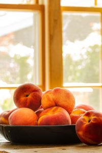 peaches in a navy blue bowl in front of a window