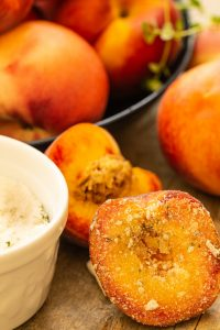 a bowl of peaches with a half of peach dipped in sugar with thyme