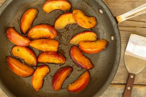 a nonstick skillet with caramelized peach slices