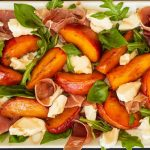 Large rectangular white dish with a salad containing caramelized peaches, prosciutto, fresh mozzarella, and basil