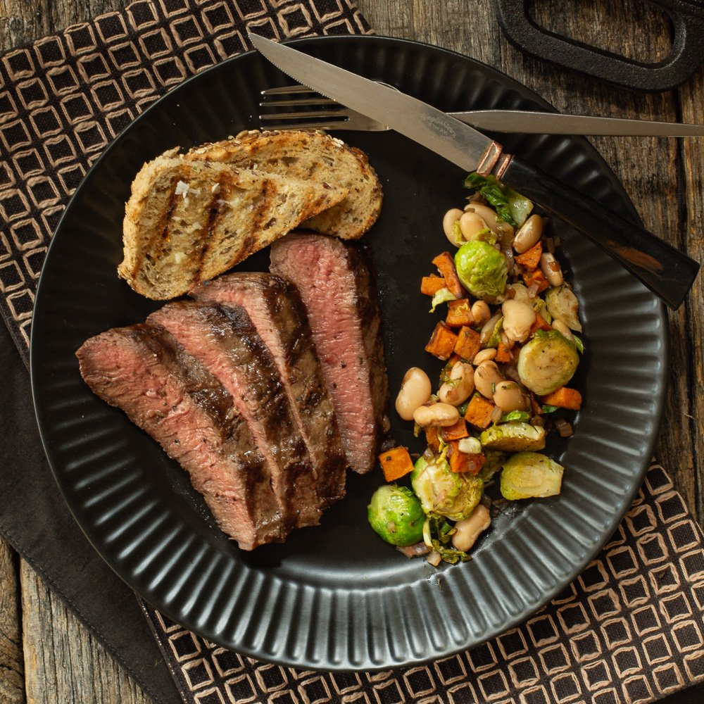 black plate with fanned slices of steak and a vegetable side of sweet potatoes, brussels sprouts, and white beans