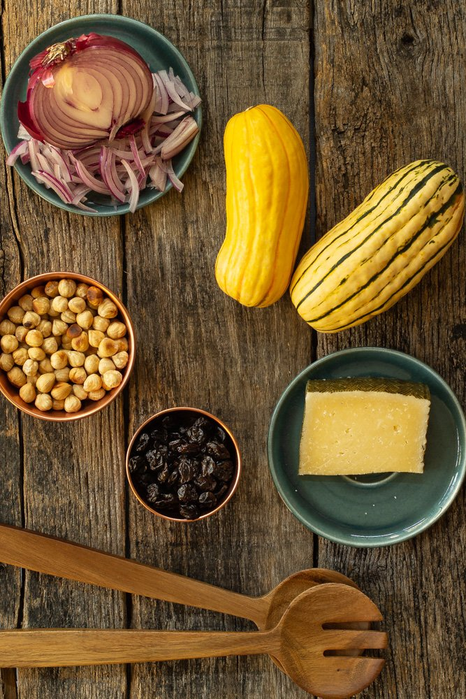 sliced red onion, roasted hazelnuts, dried red cherries, delicata squash, and manchego cheese on a wooden board