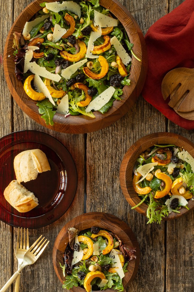 A large bowl of fall harvest salad with smaller bowls surrounding it