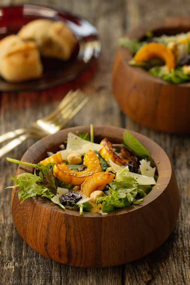 Small bowl of salad with a plate of bread in the background next to another bowl