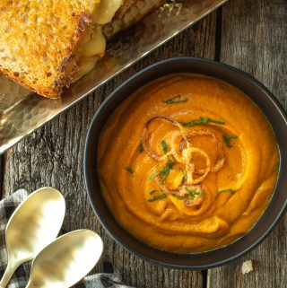 a black bowl with carrot soup with a grilled cheese to the side