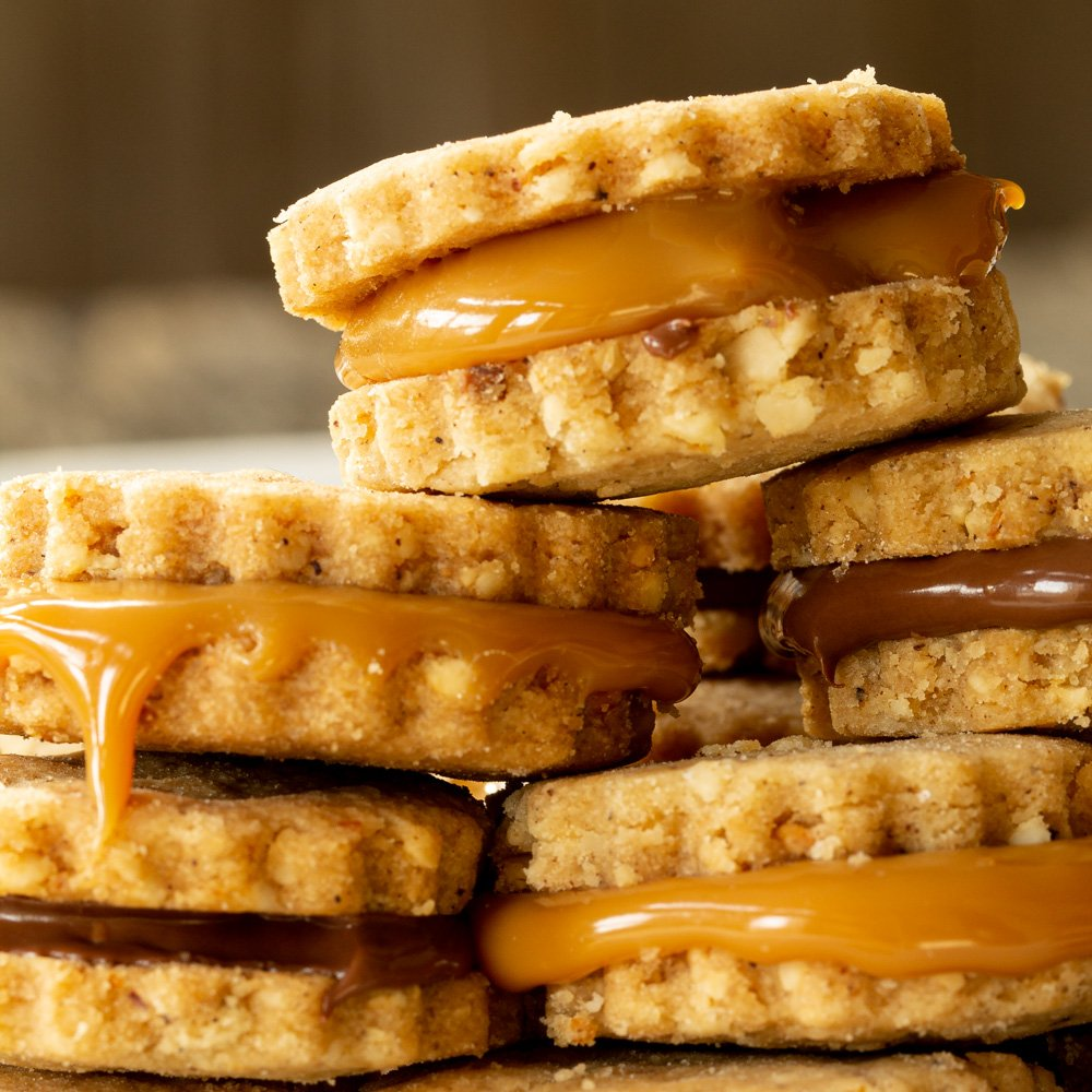 A stack of filled hazelnut and brown butter sandwich cookies on a white plate