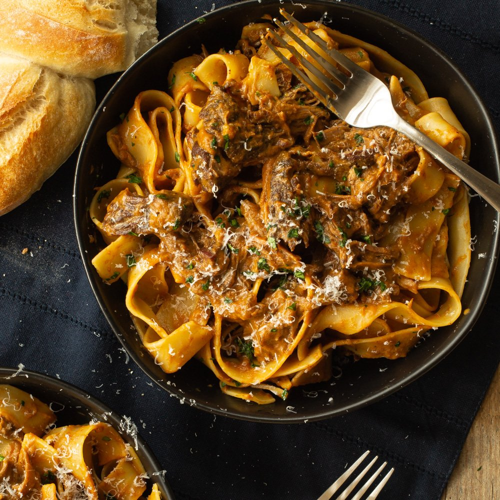 bowl of pasta with bread on the side