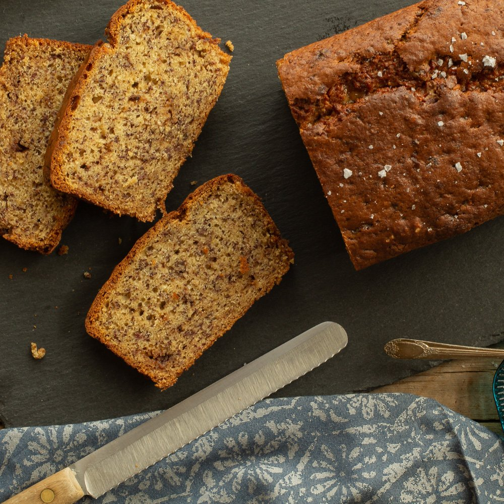 half of a loaf of banana bread with slices next to it
