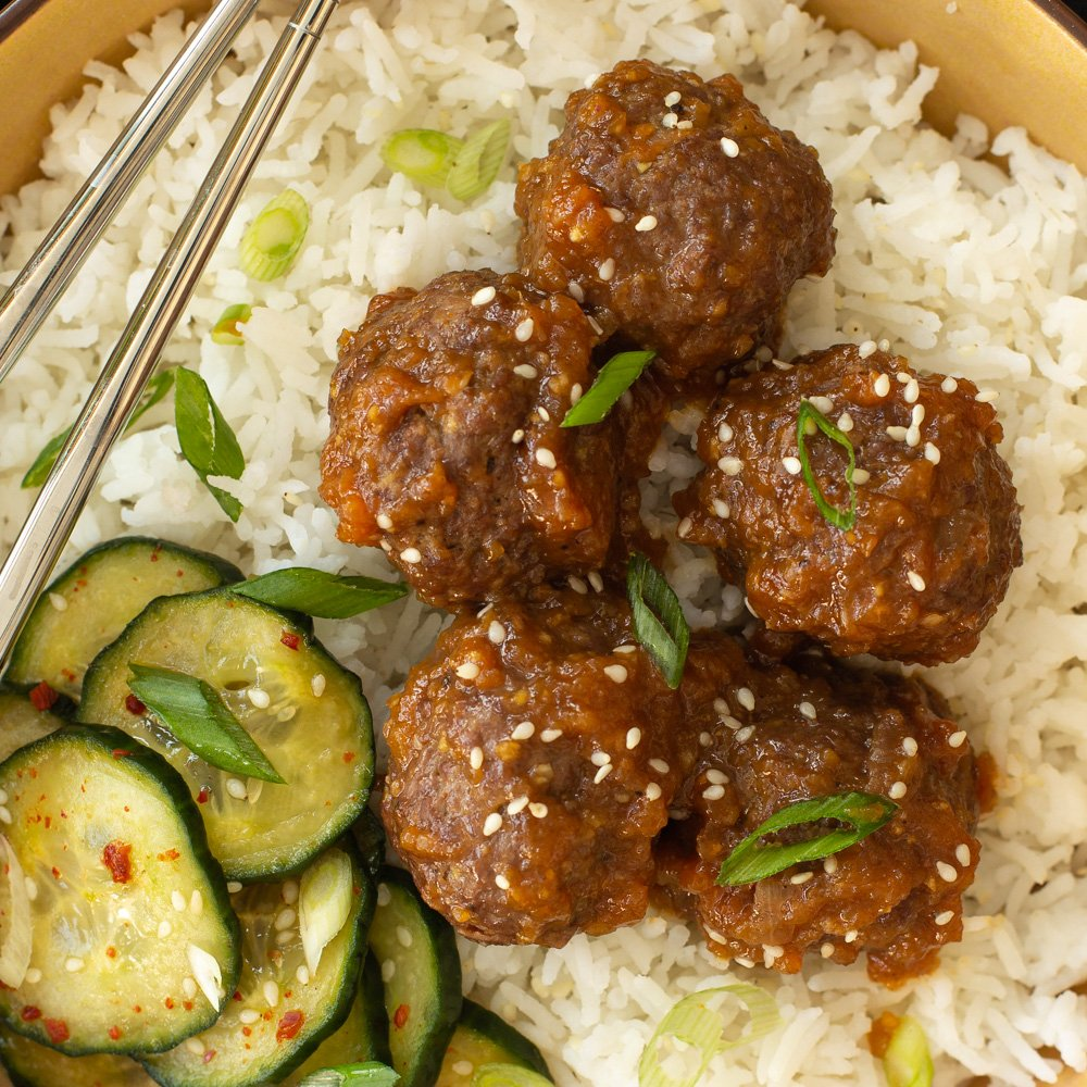 bowl of rice with meatballs and cucmbers