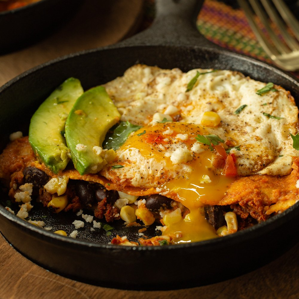 A cast iron skillet with chilaquiles filed with black beans, chorizo, and roasted corn, topped with a fried egg which is dripping yolk