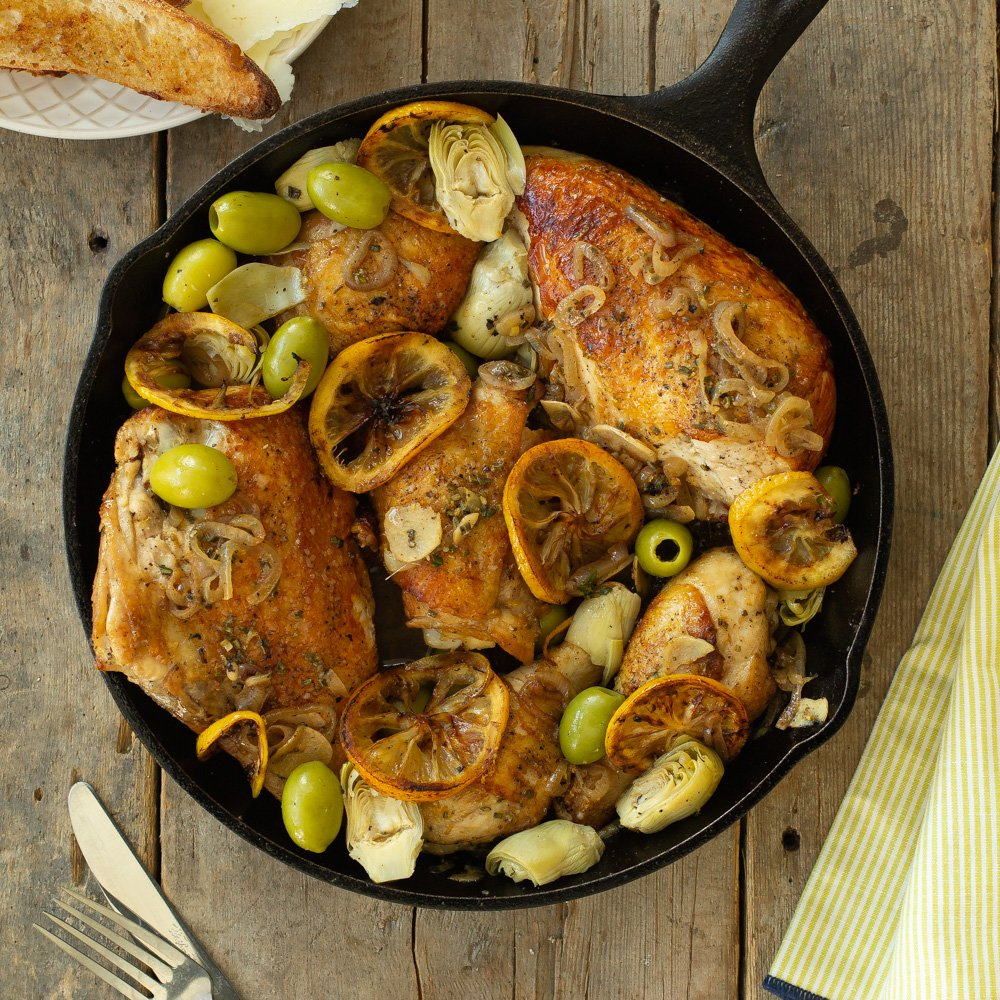 cast iron skillet filled with roasted chicken, lemons, green olives, shallots, and artichoke hearts