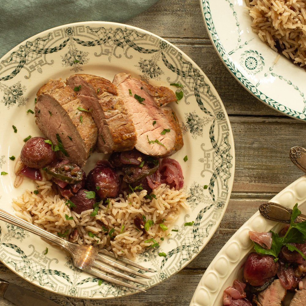 a plate with slices of pork tenderloin with pecan rice and roasted grape sauce