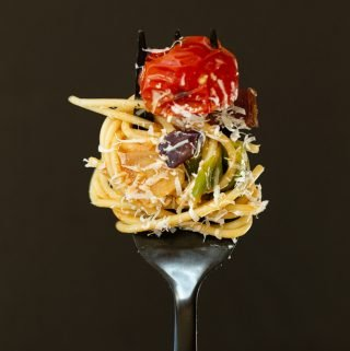 pasta with roasted eggplant, cherry tomato and escarole spooled around a black fork