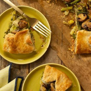 two chartreause plates with a slice of Savory Asparagus and Ricotta Galette next to a full galette