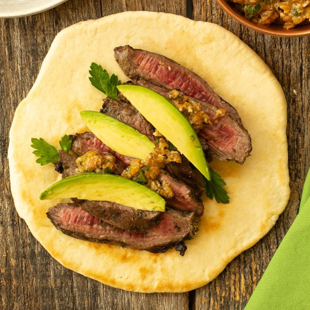 a flat bread topped with sliced steak, vegetable pesto, and avocado