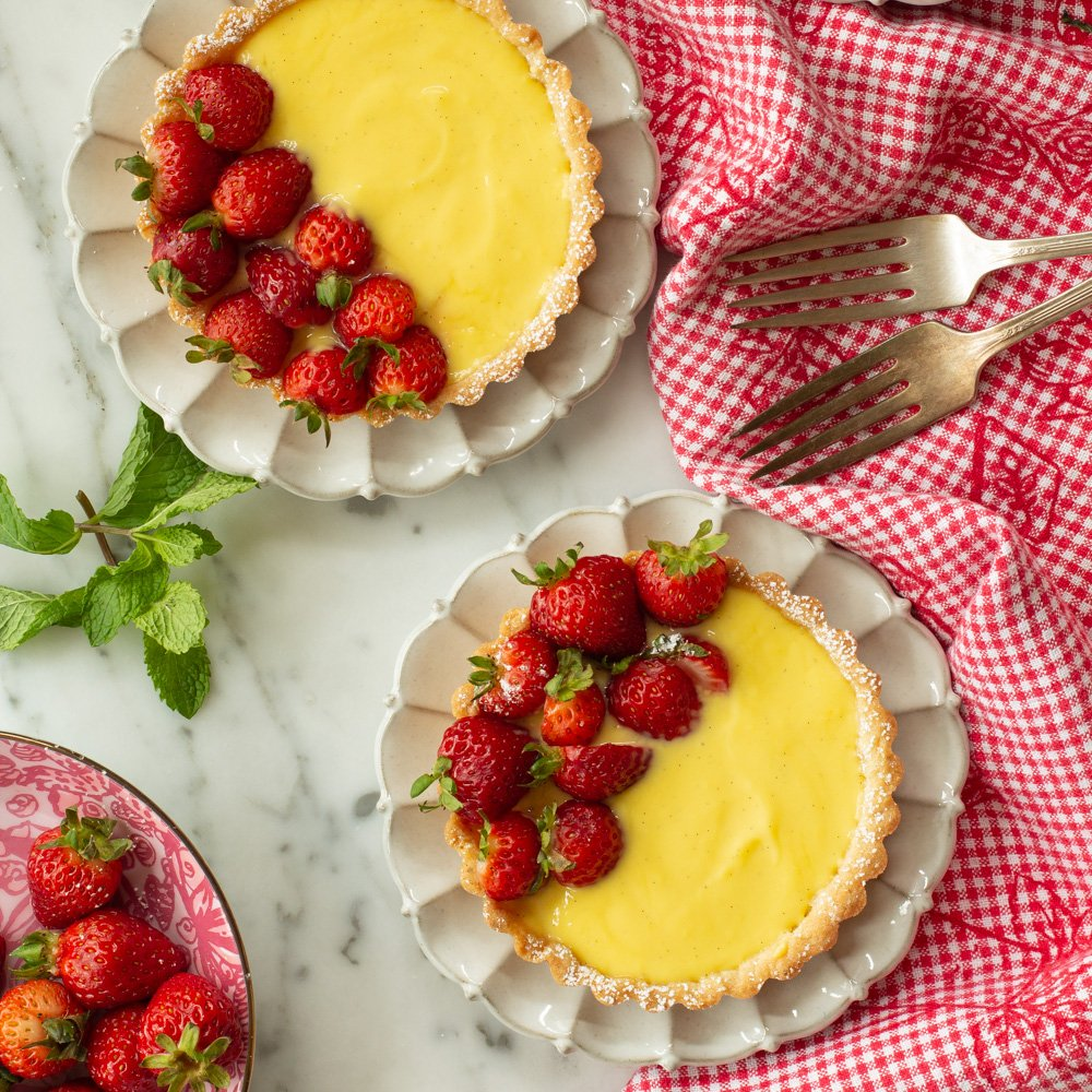 Mini Strawberry Buttermilk Tarts on white dessert plates with a red gingham table cloth