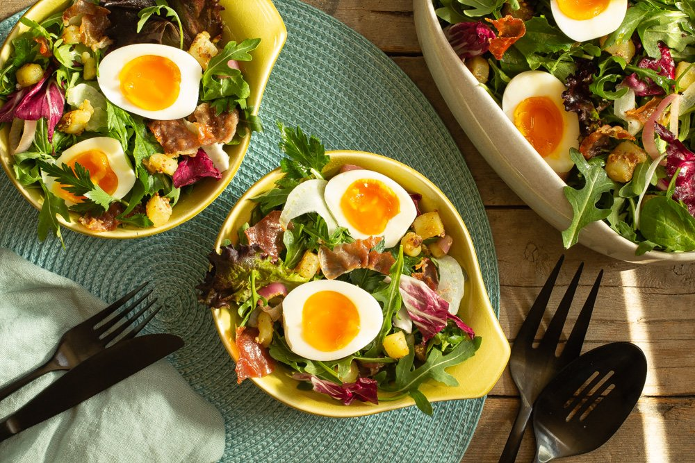 a gray serving bowl of Savory Breakfast Salad next to small chartreuse bowls of salad