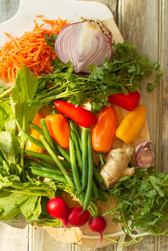 a cutting board shredded carrots, green beans, mini bell peppers, red onion, radishes, ginger, garlic, frisee, cilantro, and arugula