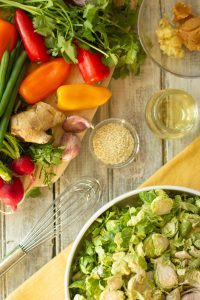 a white bowl of shredded Brussels sprouts next to salad ingredients like mini bell peppers and radishes