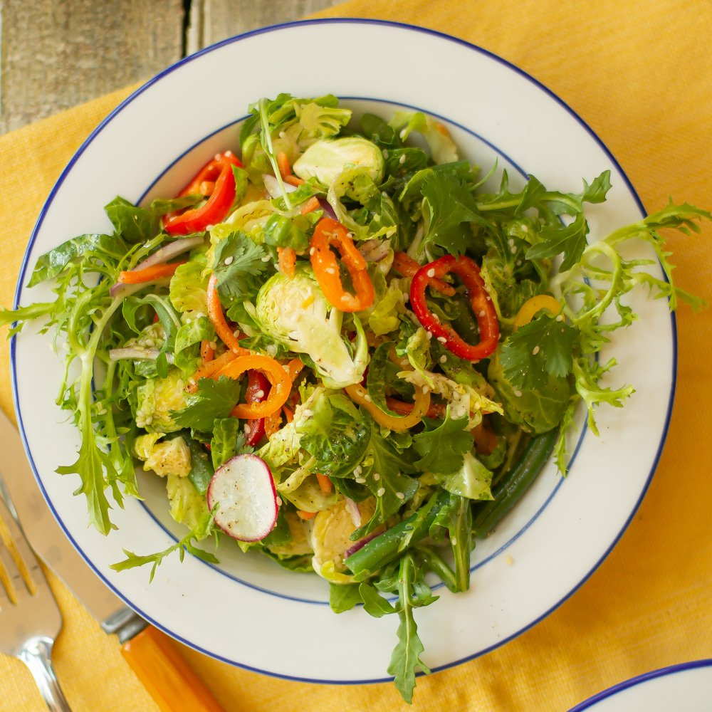 a white bowl of Shredded Brussels Sprout Salad on a yellow placemat with a fork and knive