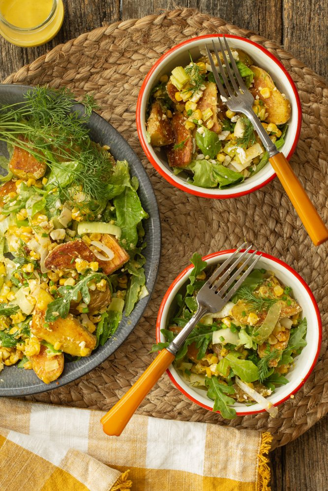 a large blue bowl of Caesar Oven-Roasted Potato Salad next to two smaller filled bowls