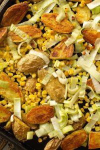 a sheet pan of roasted fingerling potatoes, corn, and leeks