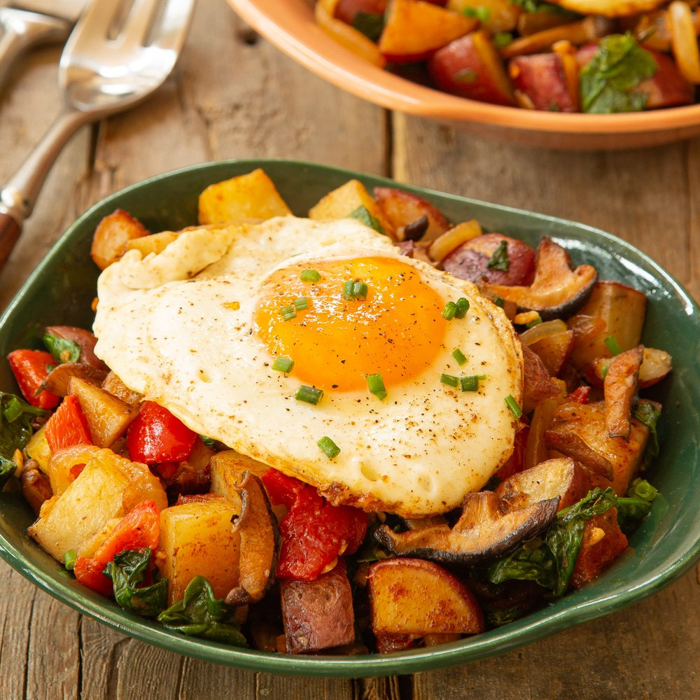 a green bowl filled with breakfast hash topped with a sunny-side-up egg.