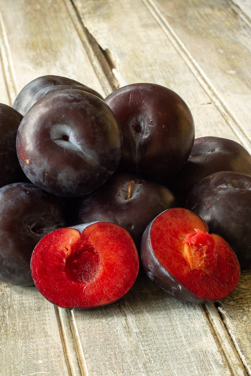 a pile of plums with a plum cut open to reveal the red fruit