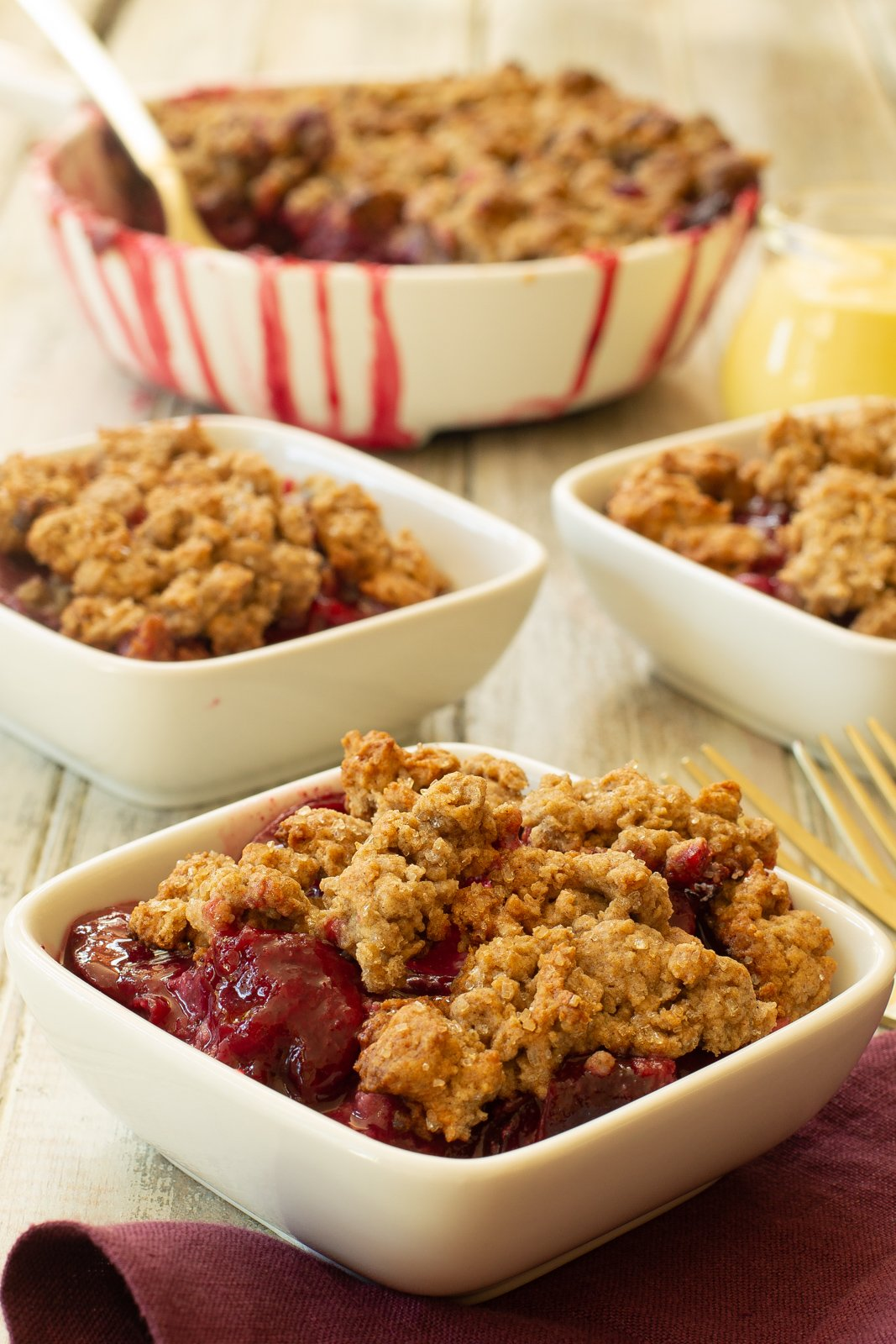 a baking dish of plum cobbler with juice running down the sides next to individual filled white bowls