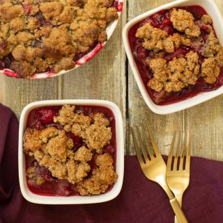 two small white bowls of cobbler next to a large baking dish