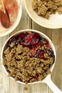 an unbaked plum cobbler with ¾ of the dough added to the top