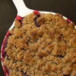 a white baking dish filled with baked plum and rye cobbler