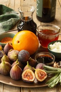ingredients for fig barbeque sauce including fresh figs, onions, garlic, sage, honey, red wine, soy sauce, and orange peel