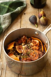 a sauce pan filled with fig sauce ingredients such as figs, red wine, onion, garlic, soy sauce, honey, and orange peel