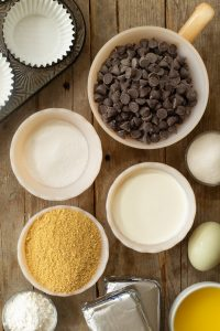 bowls of ingredients such as graham cracker crumbs, sugar, chocolate chips, an egg, corn starch, and melted butter