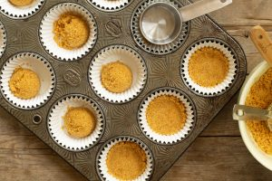 a muffin tin with cupcake liners filled with graham cracker crust