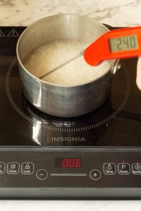 sugar syrup boiling in a saucepan with a thermometer inserted reading 240 degrees