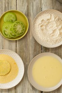plates of green tomato slices, seasoned flour, egg and buttermilk, and cornmeal
