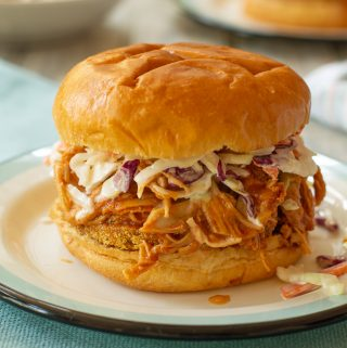 a peach barbeque pulled chicken sandwich on an enamelware plate