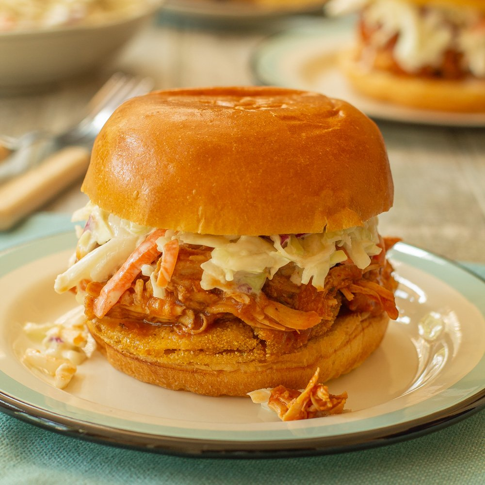 a peach barbeque pulled chicken sandwich on a enamelware plate.