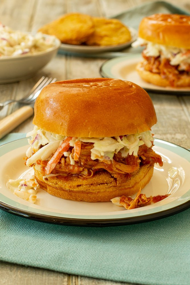a peach barbeque pulled chicken sandwich on a brioche roll made with fried green tomatoes on the bottom and cole slaw on the topl