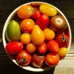 a white bowl filled with grape tomatoes of assorted colors