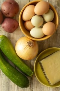ingredients such as eggs, zucchini, onions, potatoes, and Manchego cheese for a frittata