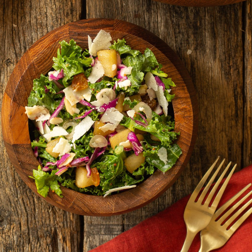 a wooden bowl full of kale and pear salad with 2 gold forks nearby