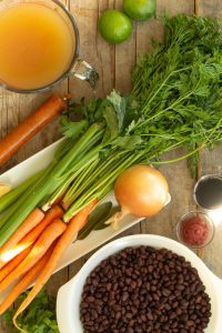 soup ingredients such as carrots, onion, celery, chicken stock, black beans, tomato paste, soy sauce, and bay leaves