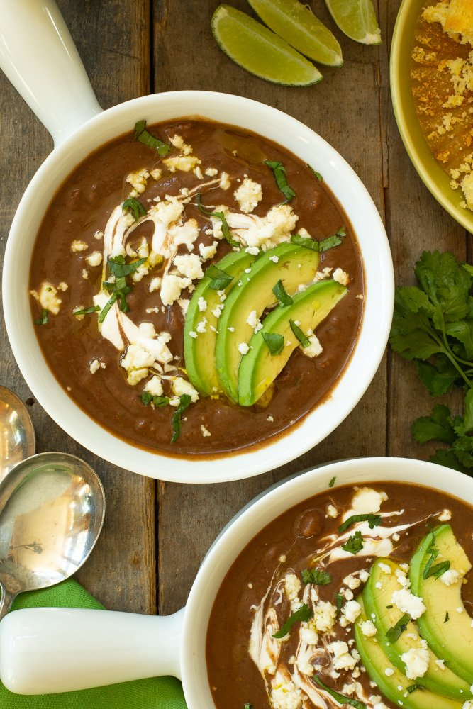 a white handled bowl filled with black bean and chorizo soup, garnished with sliced avocados, crema, queso fresco, and a drizzle of olive oil