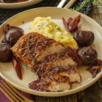 a white plate with a sliced chicken breast mashed potatoes, and mushrooms, carrots, and shallots in red wine sauce