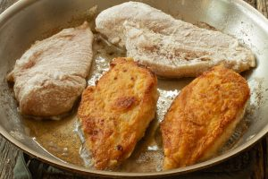 a saute pan with partially panfried chicken breasts