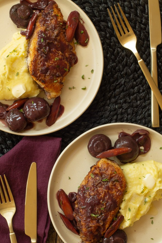 two white plates of Chicken in Red Wine Sauce with mashed potatoes