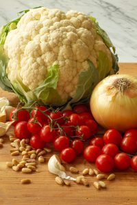 ingredients for pasta recipe such as cauliflower, onion, garlic, grape tomatoes, and pine nuts